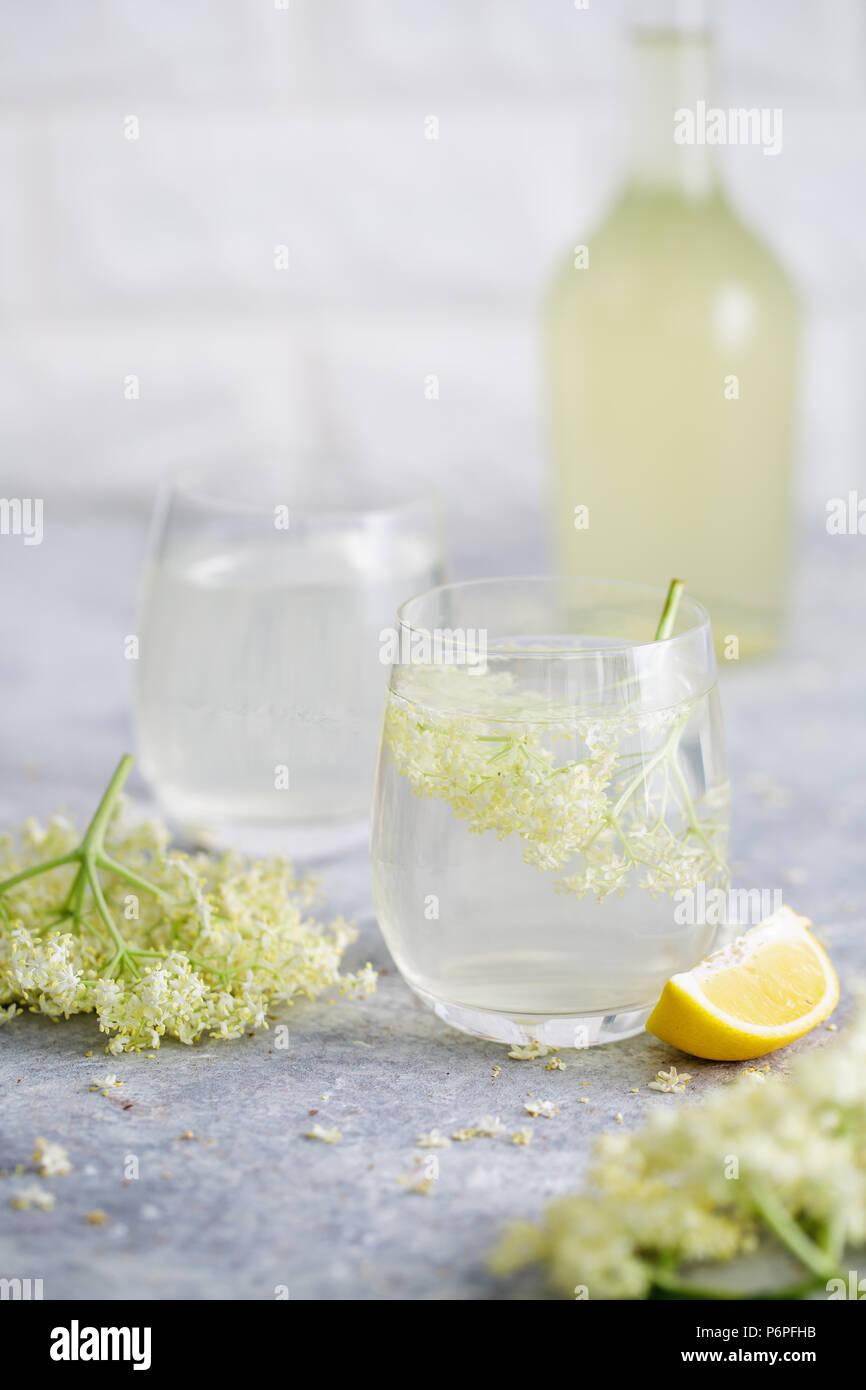 Un verre de limonade de sureau fait maison avec elderflowers fraîchement cueillis. Les fleurs sont comestibles et peuvent être utilisés pour ajouter de la saveur et l'arôme à la fois dri Photo Stock