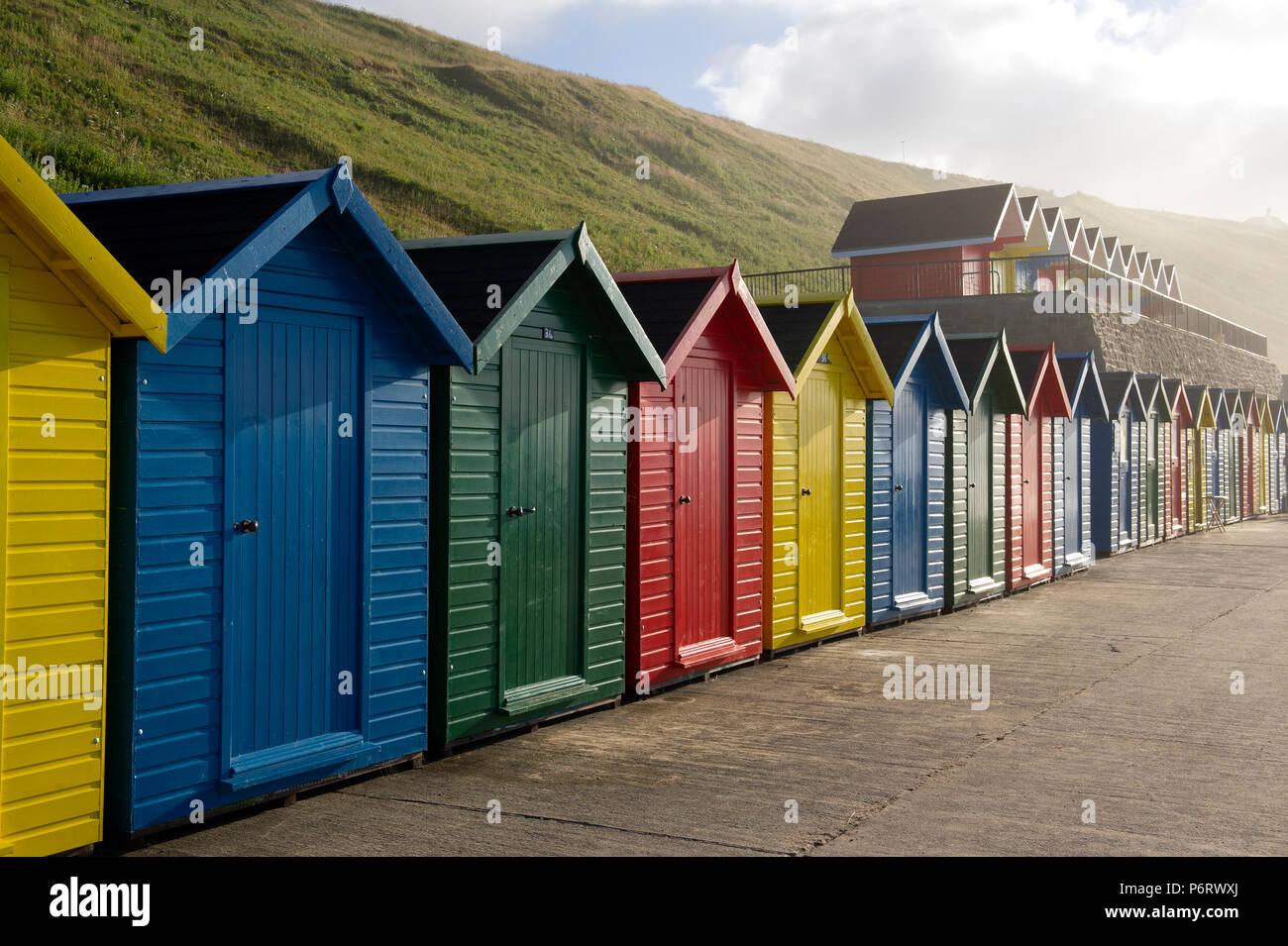 Les cabines de plage multicolores surplombant la plage de Whitby sur la côte du Yorkshire du Nord. Banque D'Images