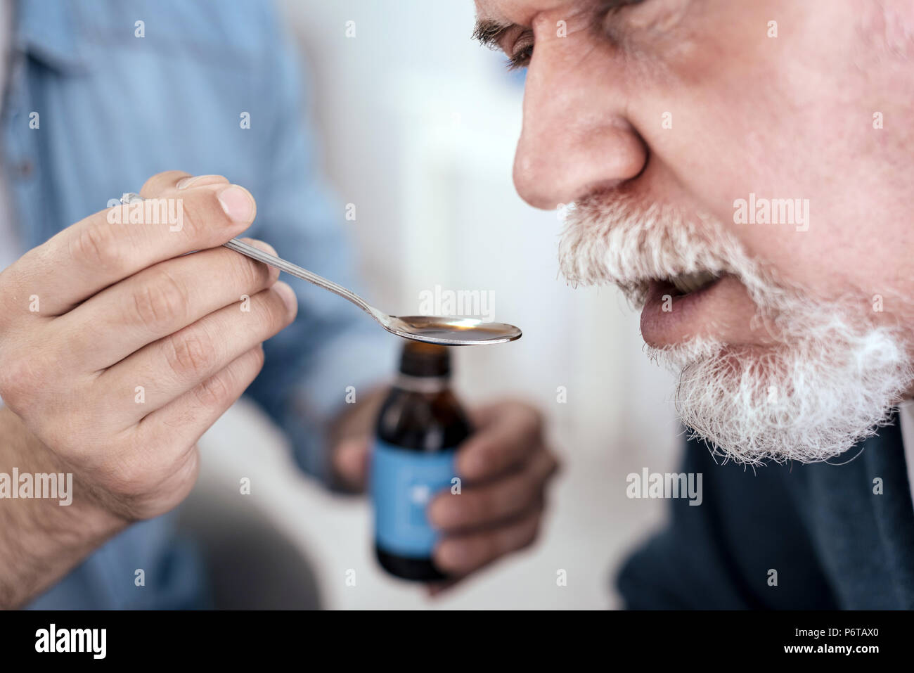 Mauvais senior man drinking med Photo Stock