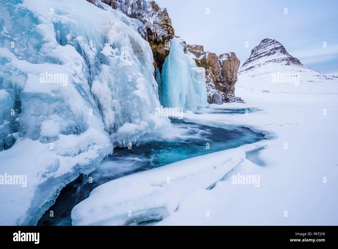 La péninsule de Snaefellsness, dans l'ouest de l'Islande, l'Europe. Chute d'Kirkjufellfoss congelés en hiver avec Kirkjufell mountain dans la toile. Photo Stock