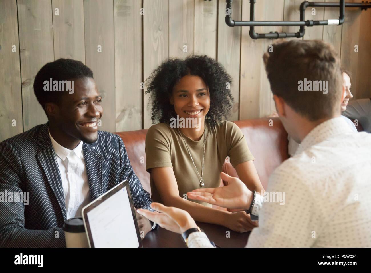 Consultant du Caucase de parler à des clients noirs in coffee shop Photo Stock