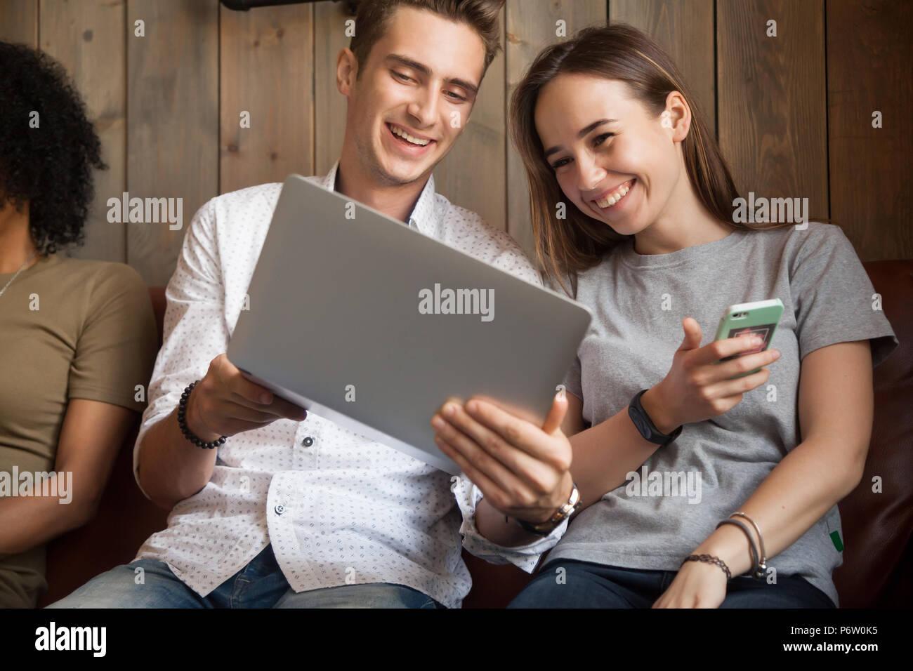 Friends laughing at millénaire vidéo drôle assis dans cafe toget Photo Stock