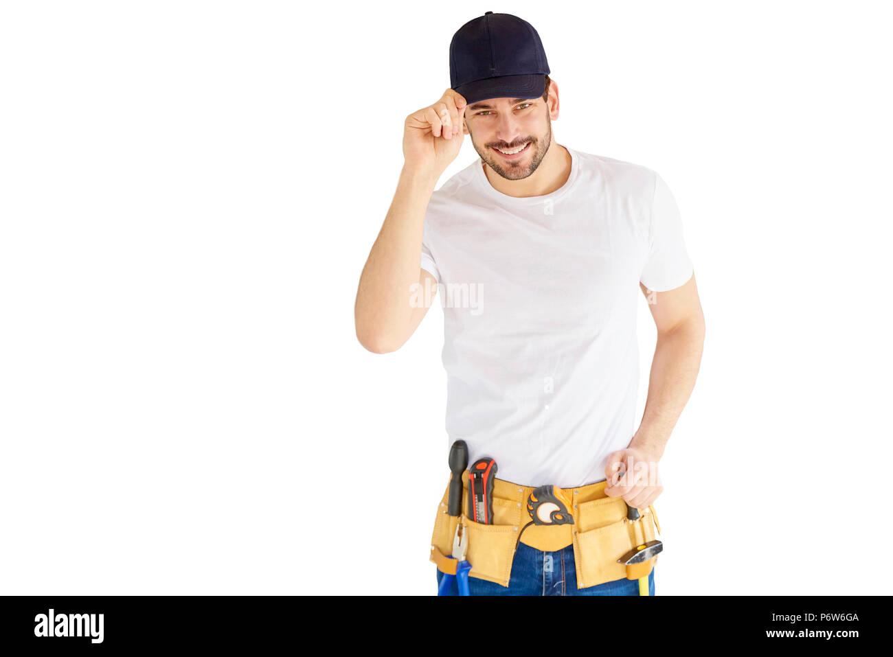 88523b5047a9 Portrait of handsome handyman wearing baseball cap et ceinture d outils  tout en se tenant au fond blanc isolé avec copie espace.