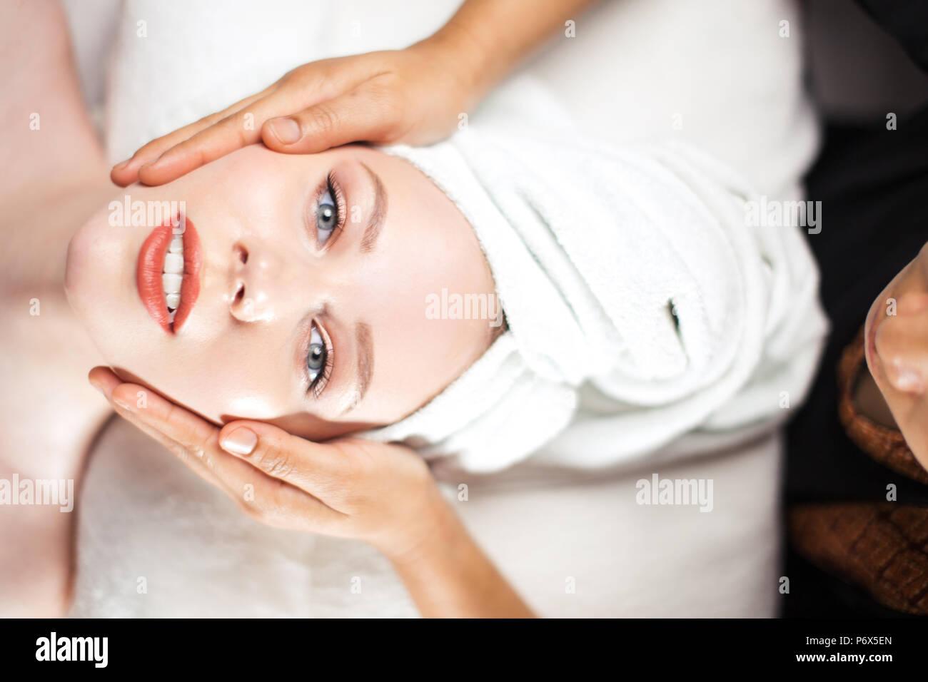 Vue de dessus, close-up of young woman getting massage visage traitement au spa de beauté salon de coiffure. Située à table de massage ,looking at camera. Photo Stock