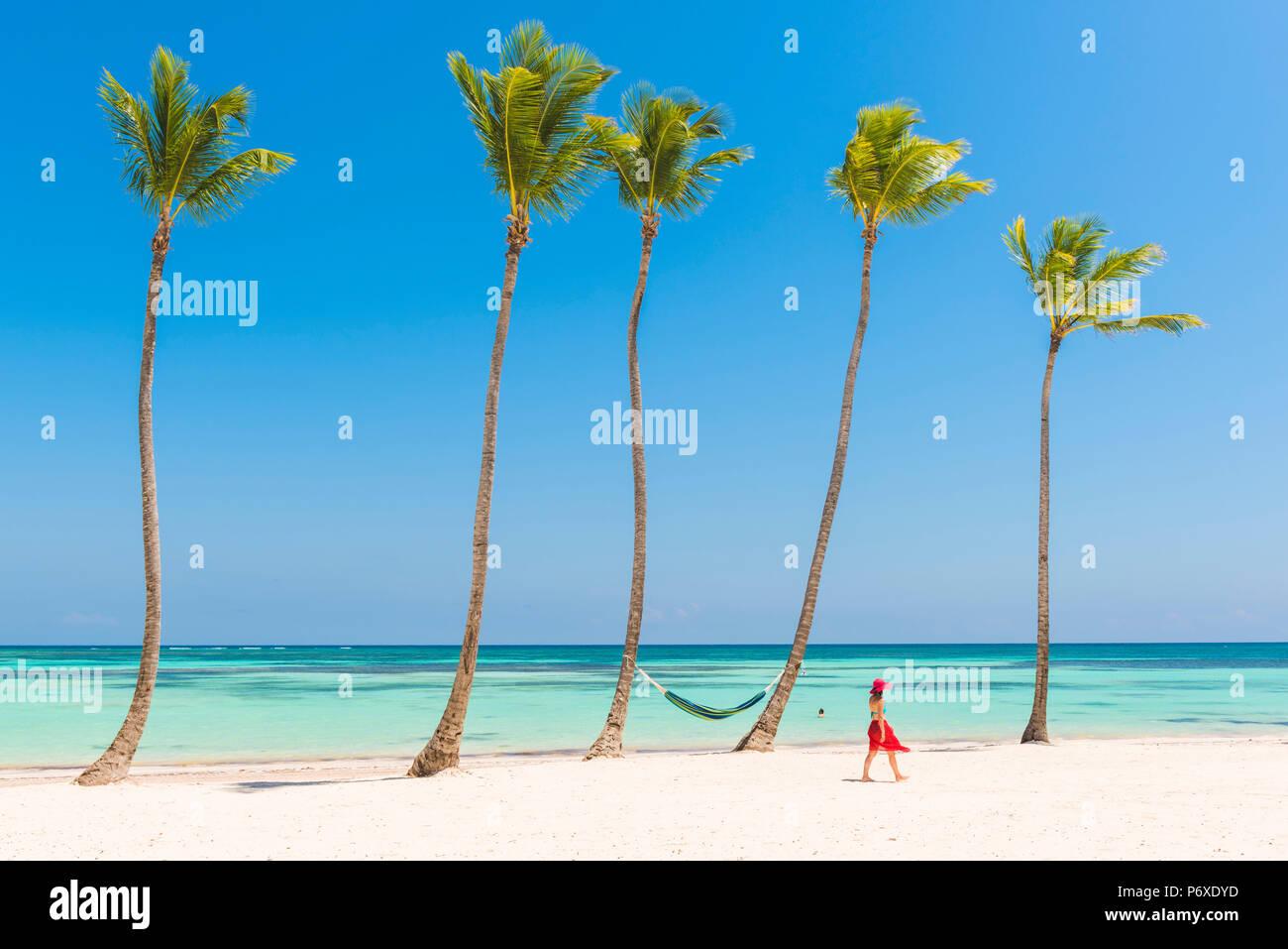 Juanillo Beach (playa Juanillo), Punta Cana, République dominicaine. Femme marche sur une plage bordée de palmiers (MR). Photo Stock