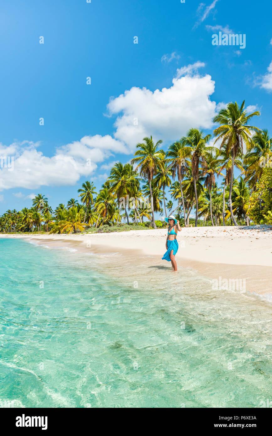 Canto de la Playa, l'île de Saona, à l'Est Parc National (Parque Nacional del Este), la République dominicaine, la mer des Caraïbes. Belle femme sur une plage bordée de palmiers (MR). Photo Stock