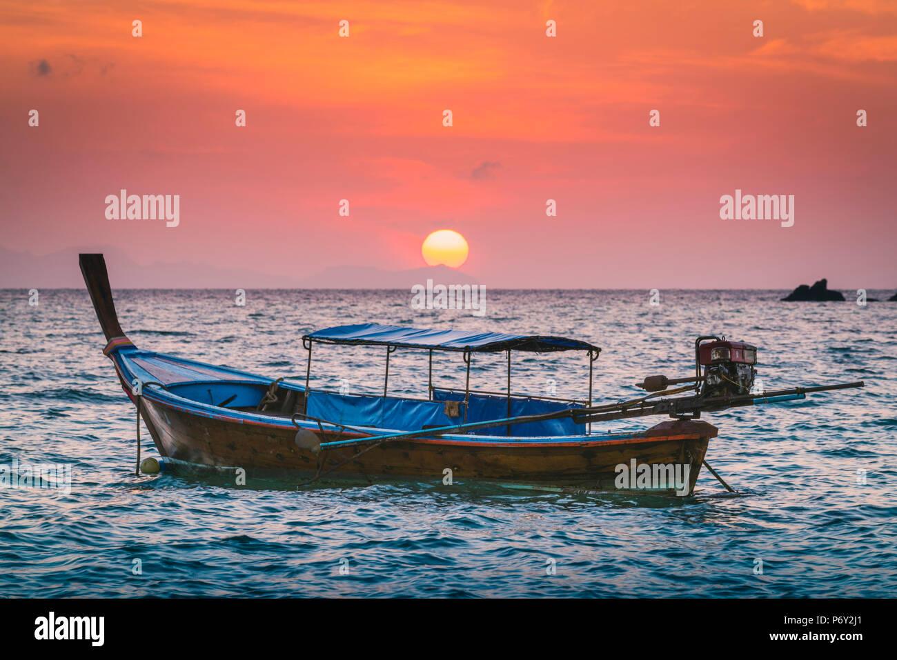 Bateaux Longtail de Sunset Beach, Ko Lipe, Ranong, Thaïlande. Bateau longue queue traditionnels et soleil levant. Photo Stock