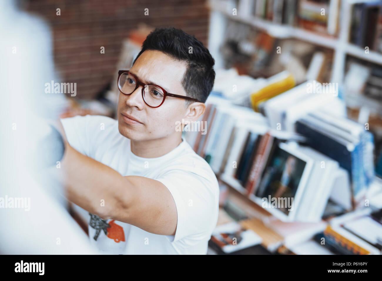 Jeune homme à lunettes main atrractive dessin de livre sur une étagère. Banque D'Images