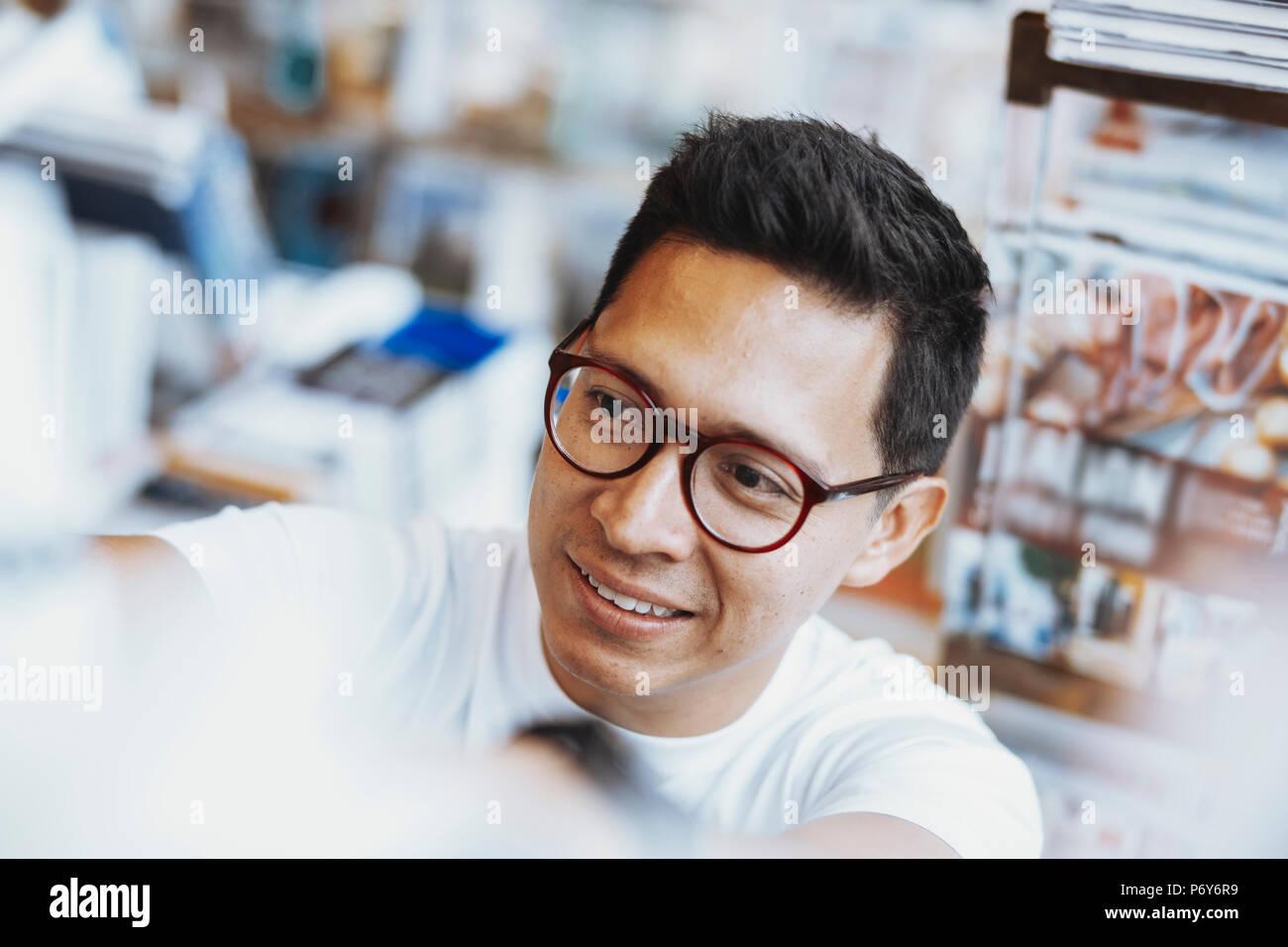 Jeune homme à lunettes atrractive livre choisir un livre sur l'étagère. Photo Stock