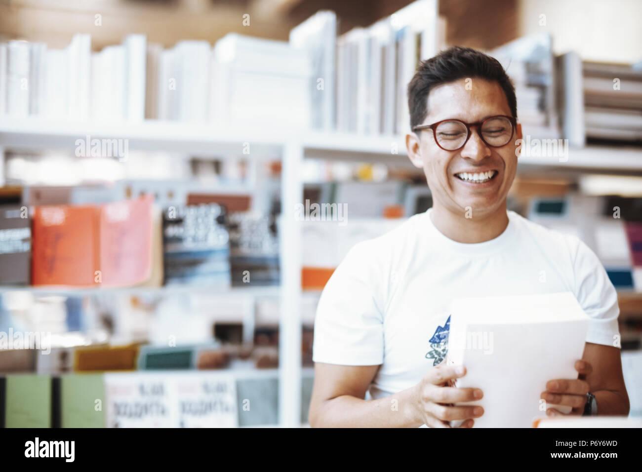 Jeune homme à lunettes heureux holding book avec cache et rire. Photo Stock