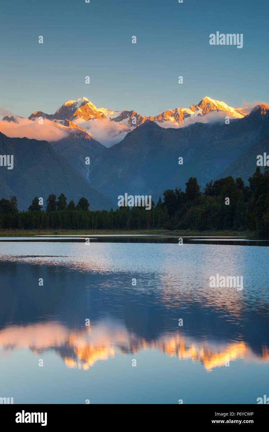 Nouvelle Zélande, île du Sud, Côte Ouest, Fox Glacier Village, Lake Matheson, reflet de Mt. Tasman et Mt. Cook, crépuscule Photo Stock