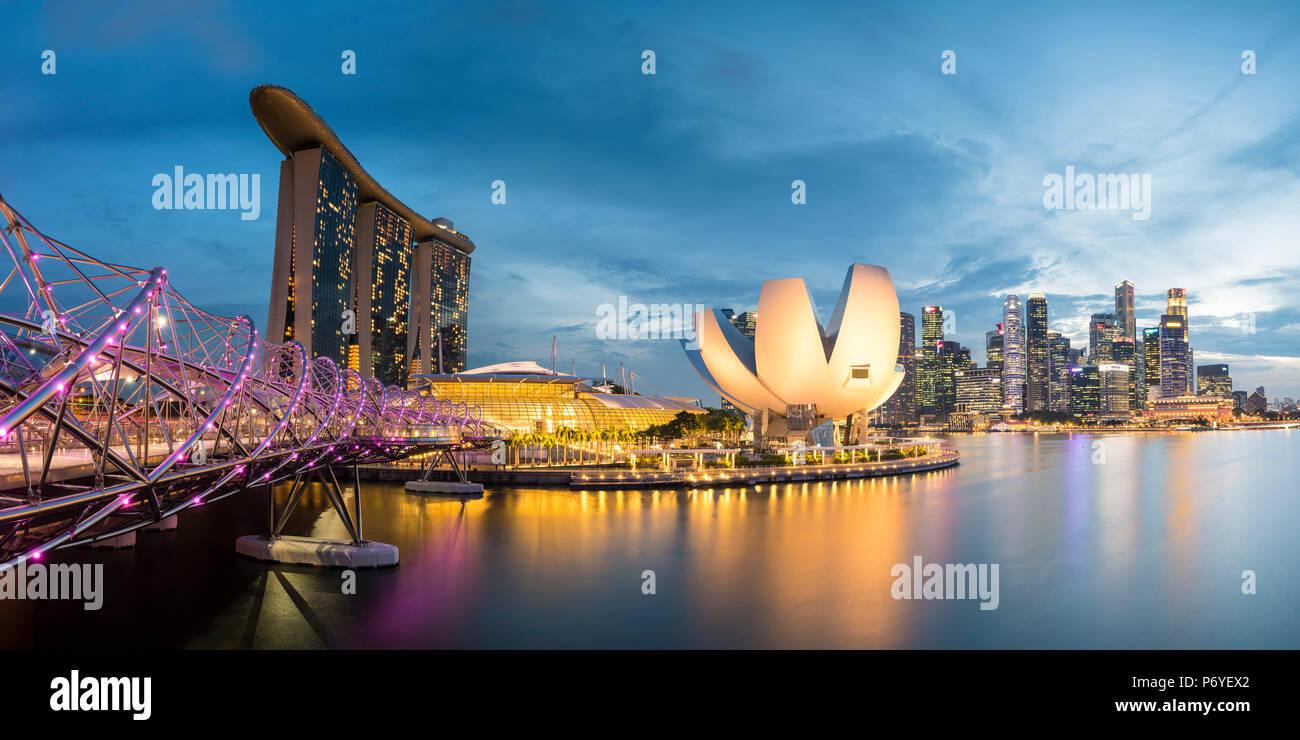 Singapour, République de Singapour, en Asie du sud-est. Vue panoramique de l'Hélix bridge, Marina Bay Sands et le musée ArtScience au crépuscule. Banque D'Images