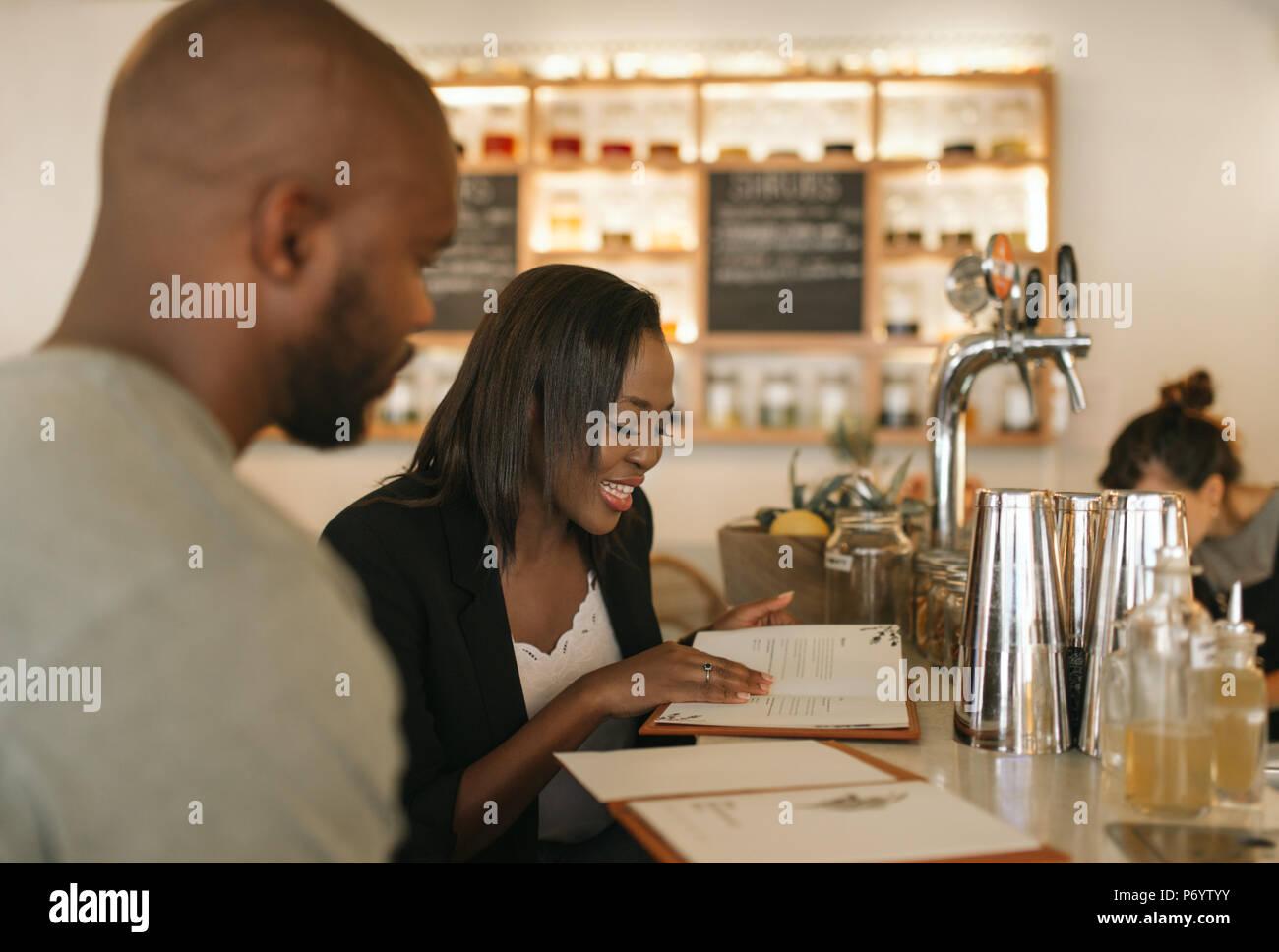 Smiling young African American couple lecture des menus dans un bar Photo Stock