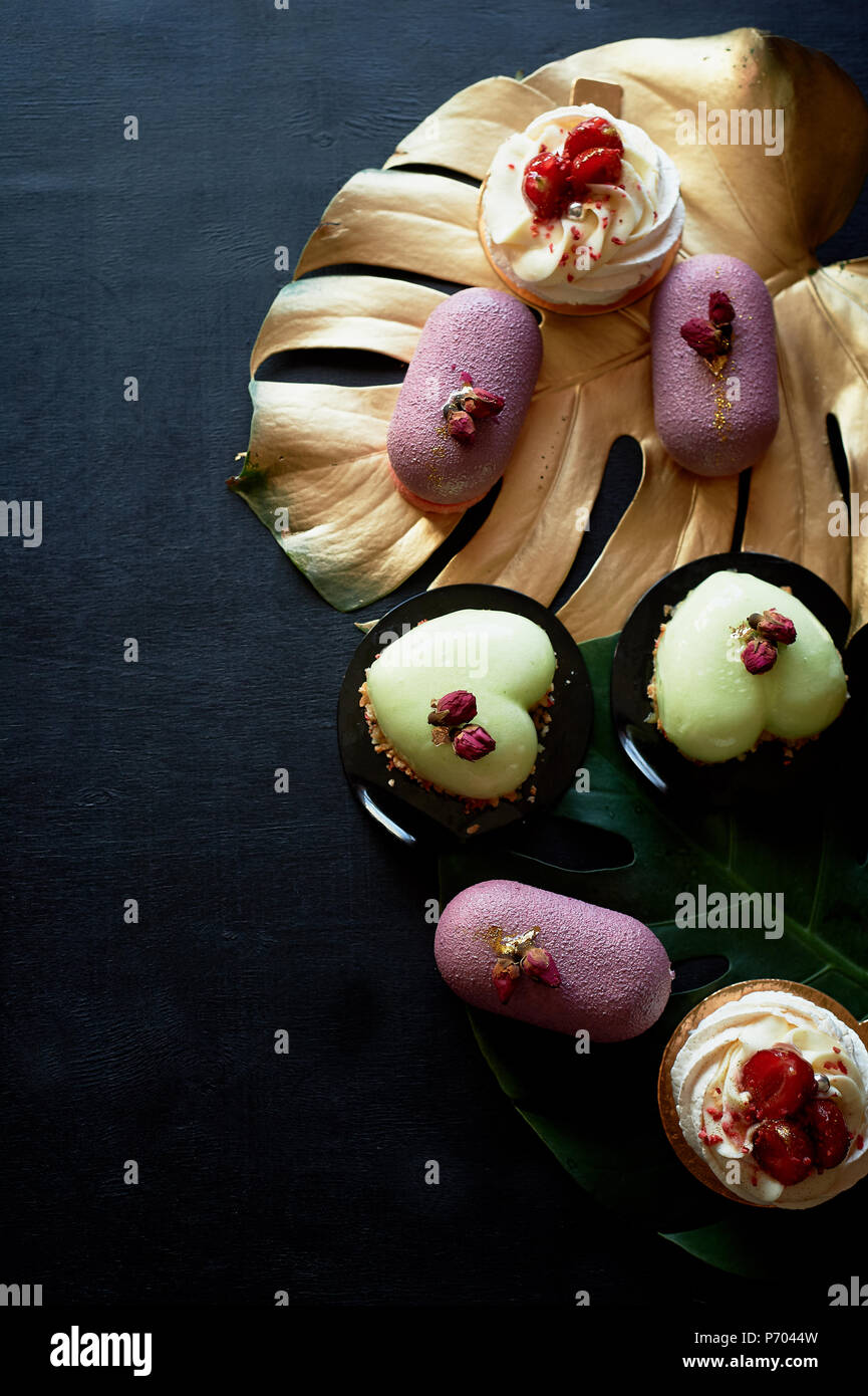 Gâteaux Moscovie violet et jaune citron. Pistache et fruits. Anna Pavlova meringuée . Art culinaire de la feuille d'or monstera Photo Stock