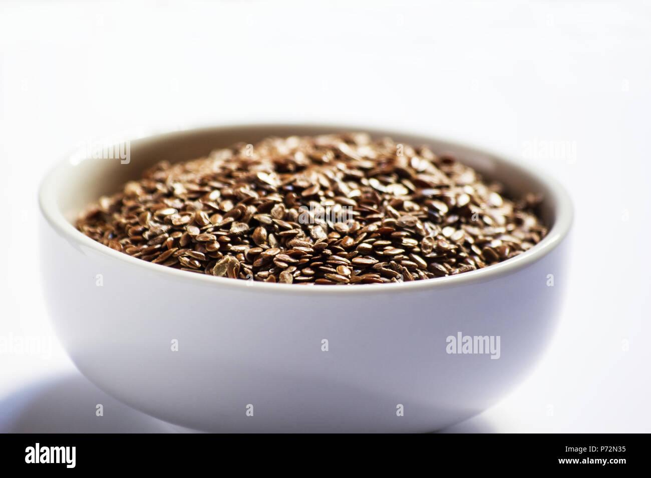 Les graines de lin dans un bol blanc sur fond blanc Photo Stock