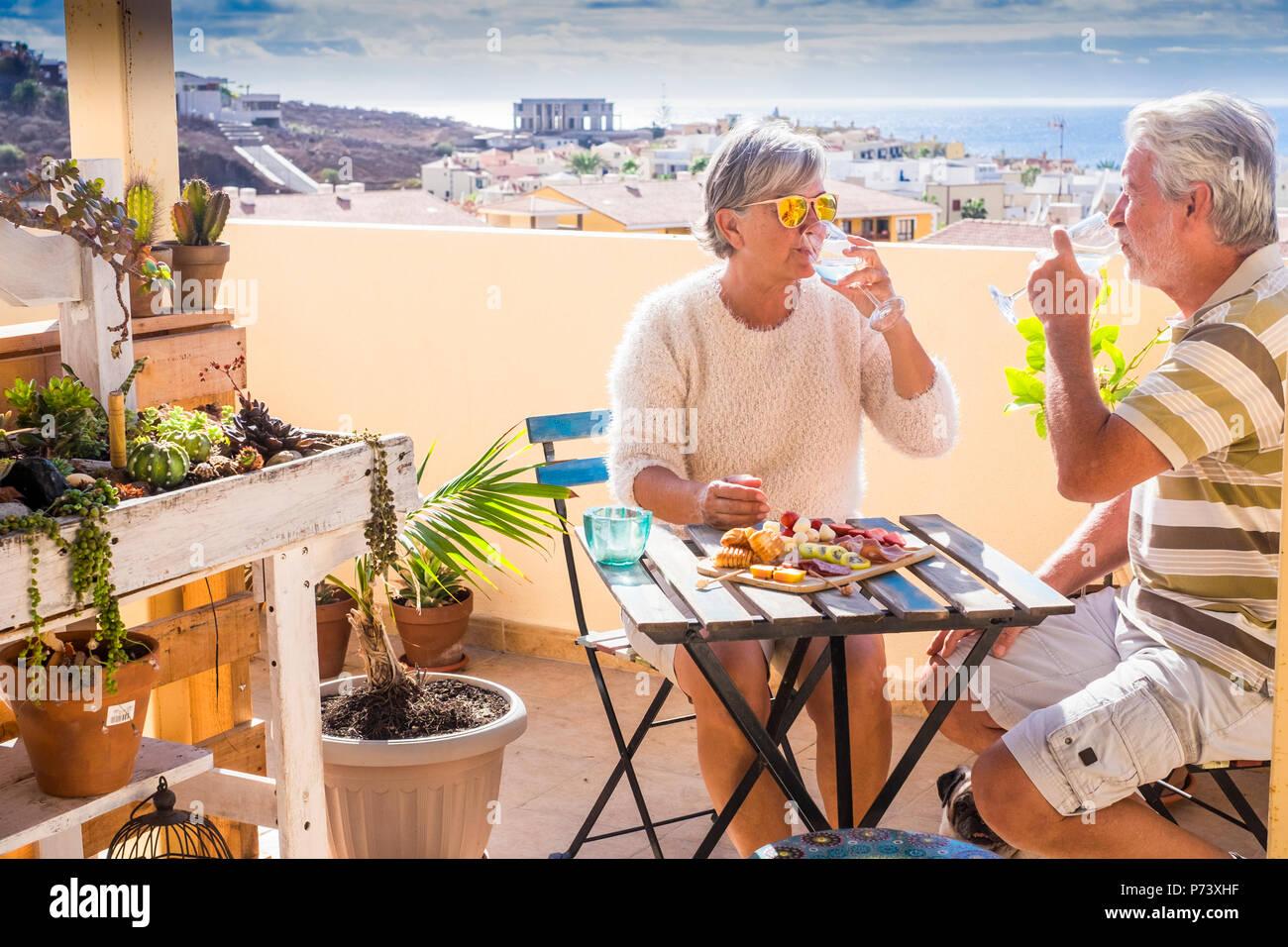 Senior caucasian couple manger et profiter ensemble de plein air loisirs boire et manger un petit-déjeuner dans un matin ensoleillé sur le toit avec vue sur l'océan Photo Stock