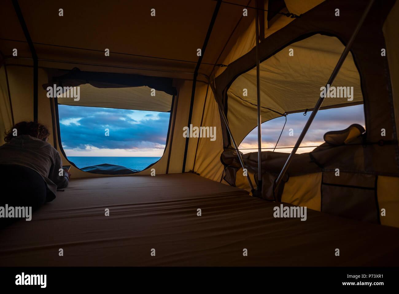 L'âge moyenne forte indépendante solitaire femme sentir la nature plein air dans une tente de toit sur la voiture. transport et le mode de vie pour de beaux concept wanderlust Photo Stock