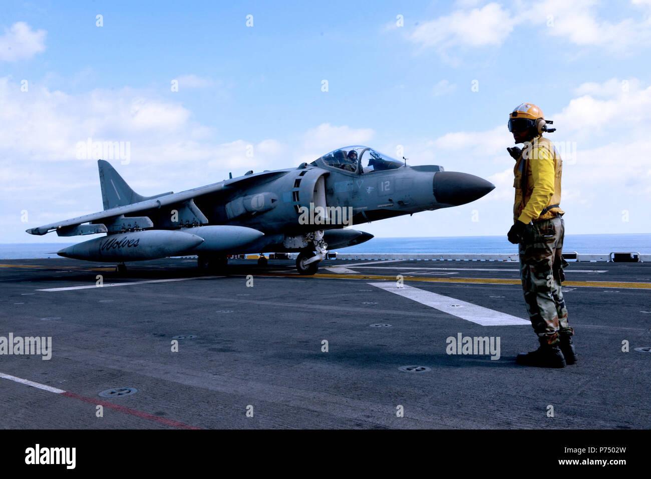 Mer (oct. 9, 2014) - Aviation maître de Manœuvre (manutention) 3e classe Andrew Sterling, de Chicago, dirige un AV-8B Harrier italien à bord du navire d'assaut amphibie USS Bataan (DG 5). Le groupe amphibie Bataan est sur un déploiement prévu des opérations de sécurité maritime, offrant une capacité d'intervention de crise et les efforts de coopération en matière de sécurité dans le théâtre de la sixième flotte américaine zone d'opérations. Banque D'Images