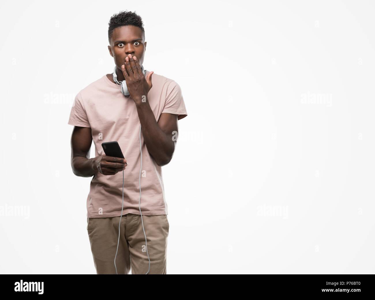 Young african american man wearing headphones holding smartphone et couvrir la bouche à part choqué avec honte pour erreur, expression de la peur, peur Banque D'Images
