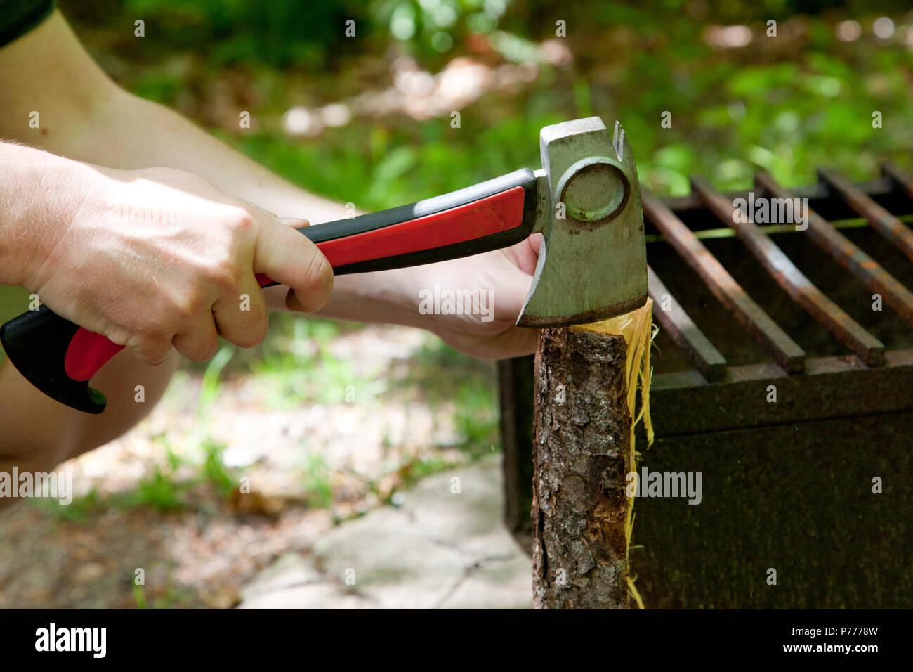 Personne crouching avec bois de chauffage Bois de fractionnement Photo Stock