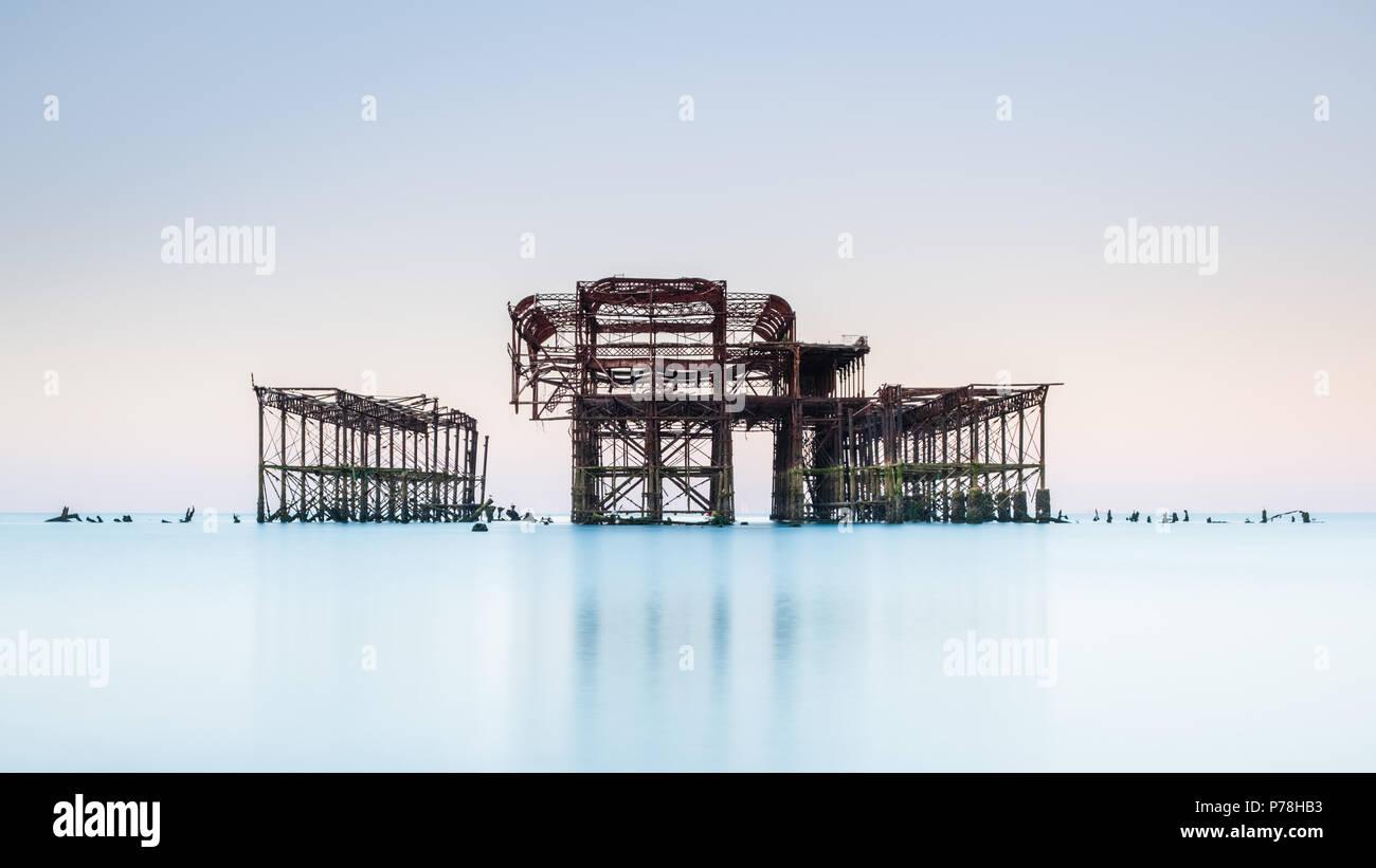 West Pier minimaliste à Brighton, East Sussex, au lever du soleil et se reflètent dans une mer calme avec de belles teintes pastel dans un ciel sans nuages Photo Stock