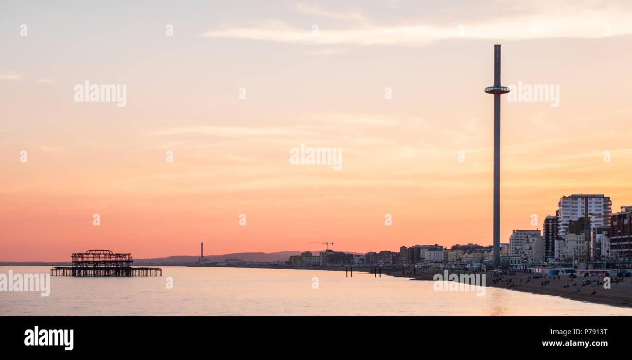 British Airways j360 et West Pier, Brighton, East Sussex, y compris le front de mer au coucher du soleil avec ciel jaune et orange intense Photo Stock