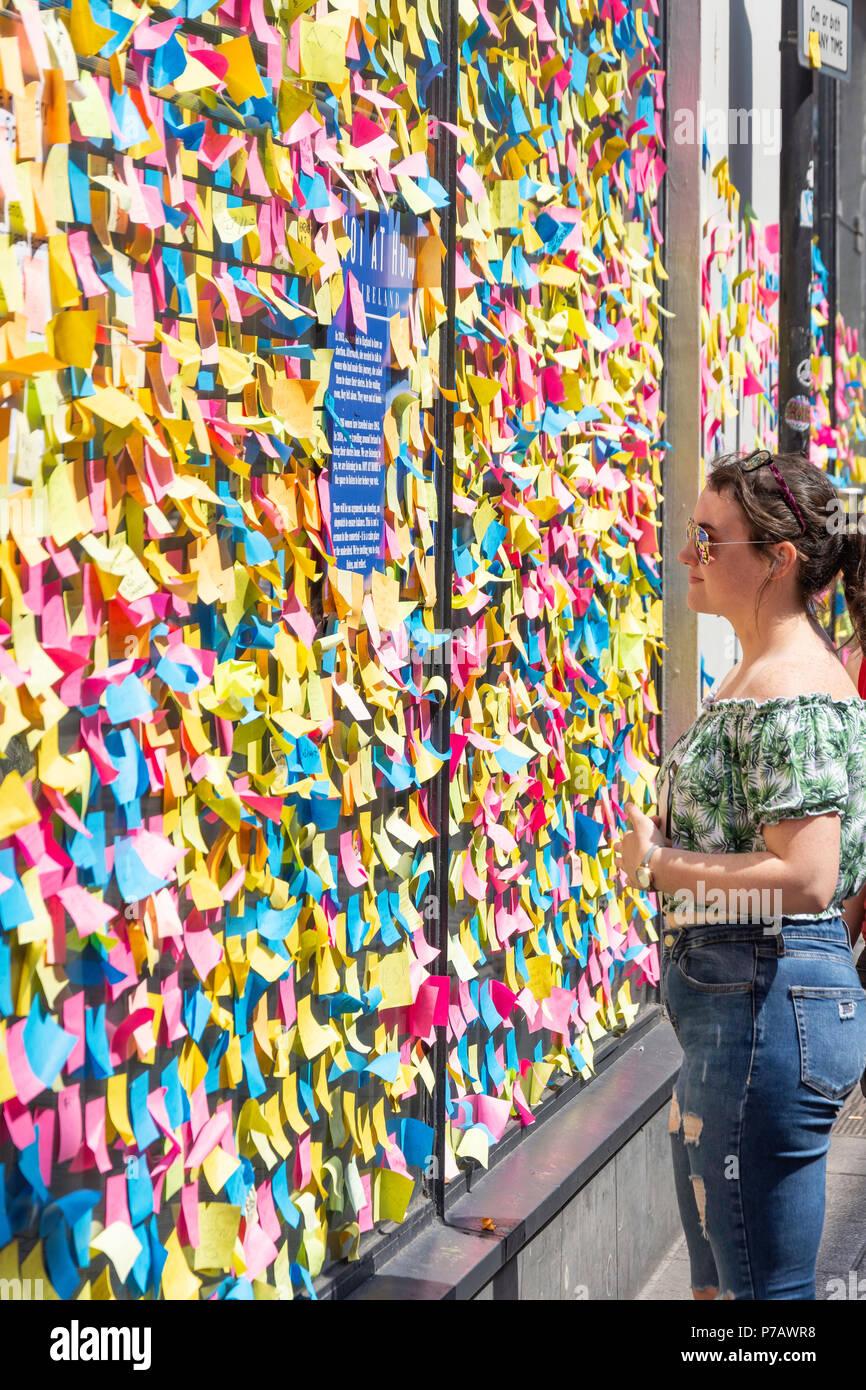 Jeune femme à la recherche au mur recouvert de post-it (référendum avortement soutien), Temple Bar, Dublin, Leinster Province, République d'Irlande Photo Stock
