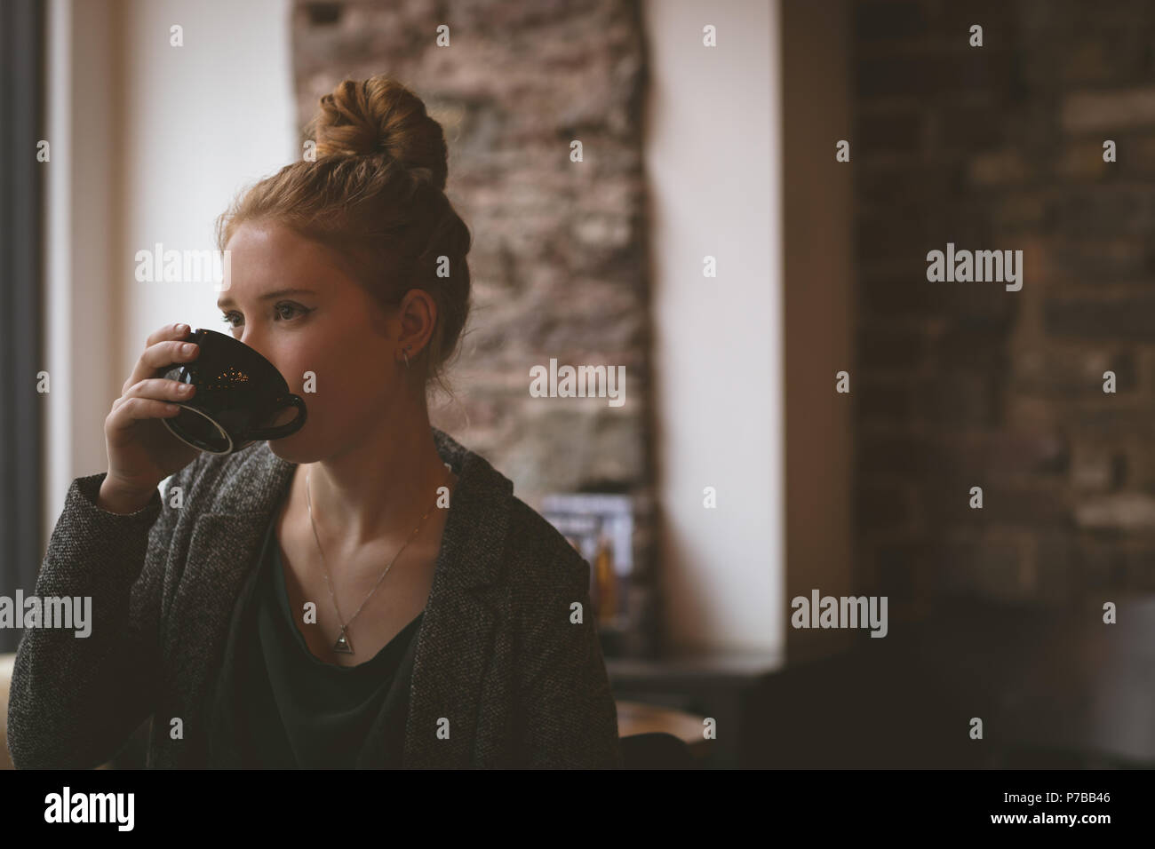 Woman having coffee at cafe Photo Stock