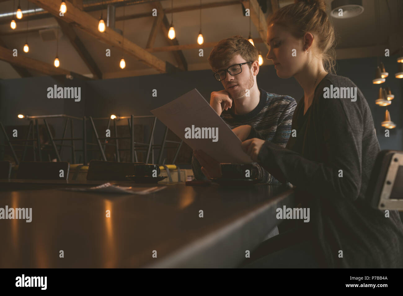 Contrôle de couple de la carte des menus au restaurant Photo Stock