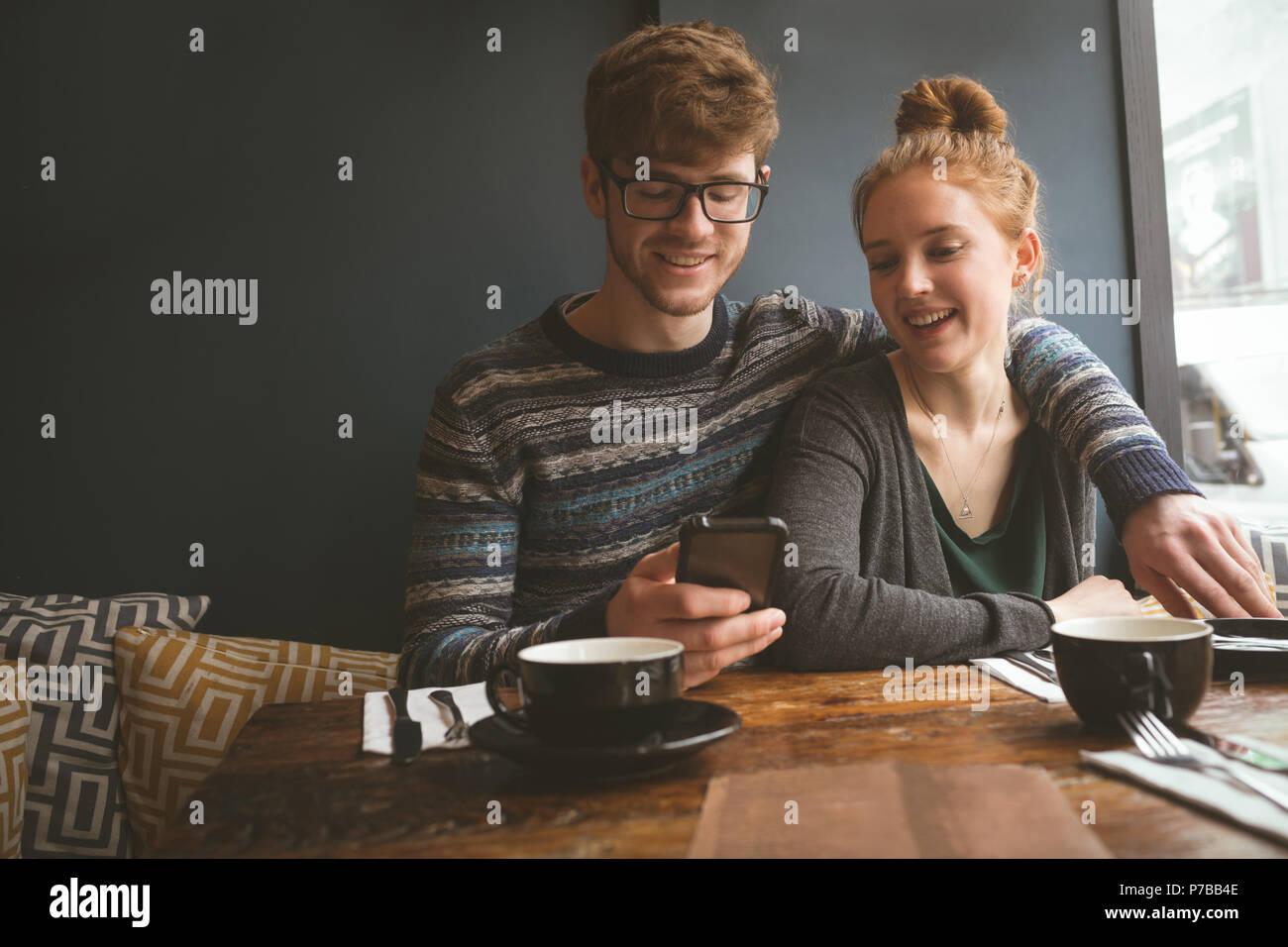 Jeune couple using mobile phone Photo Stock