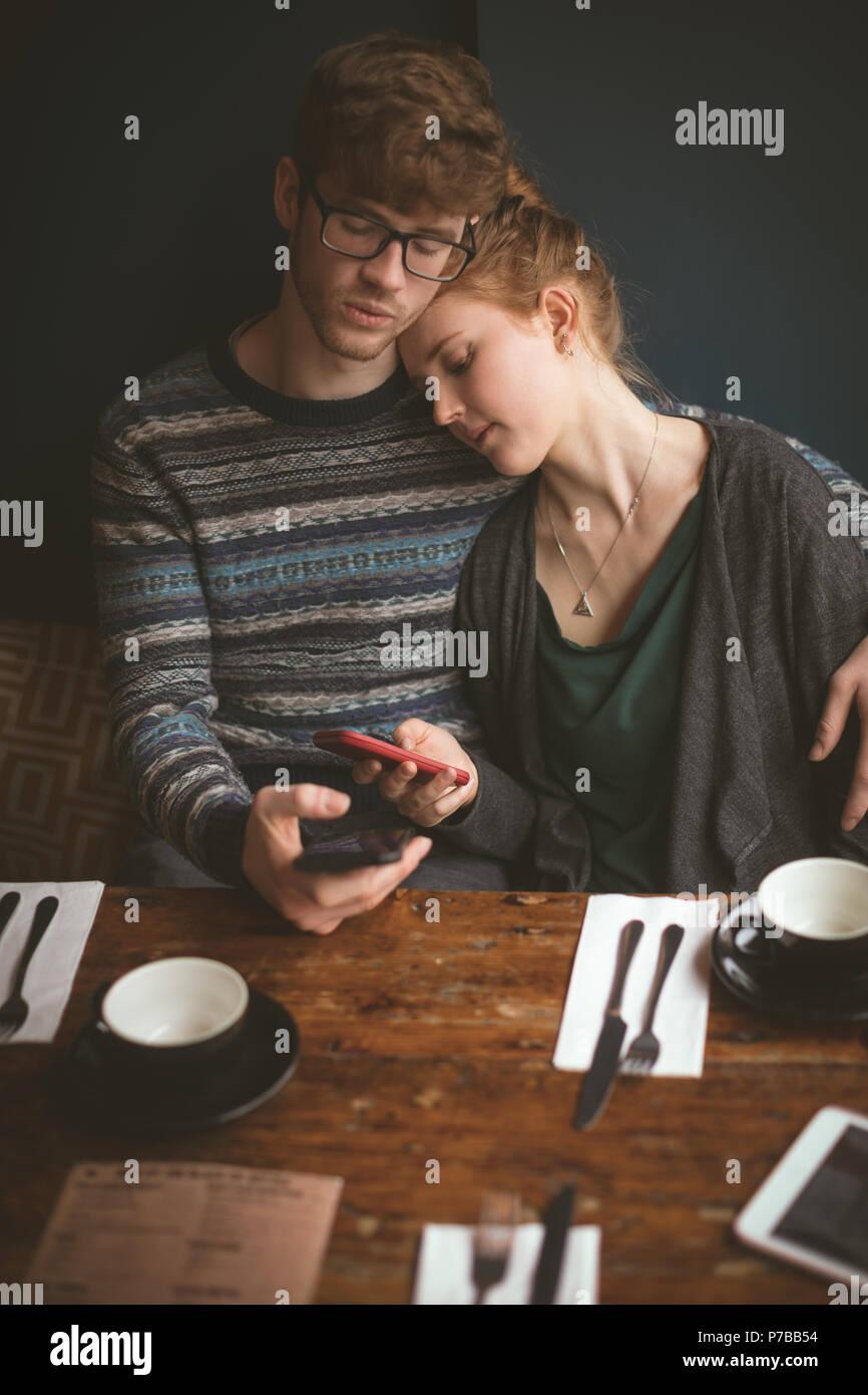 Couple et l'utilisation de téléphones mobiles dans le café Photo Stock