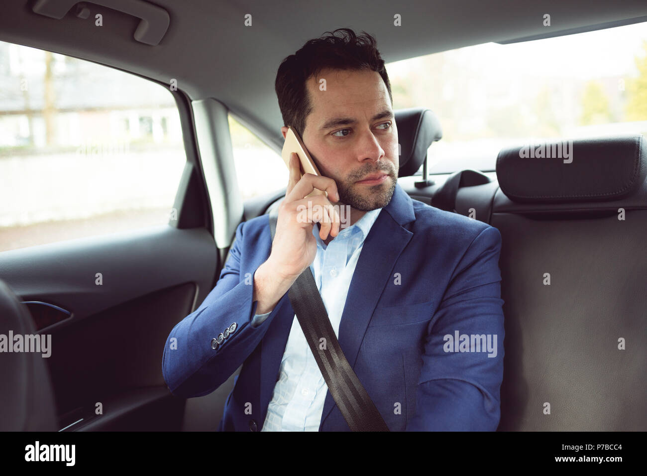 Businessman talking on mobile phone in a car Photo Stock