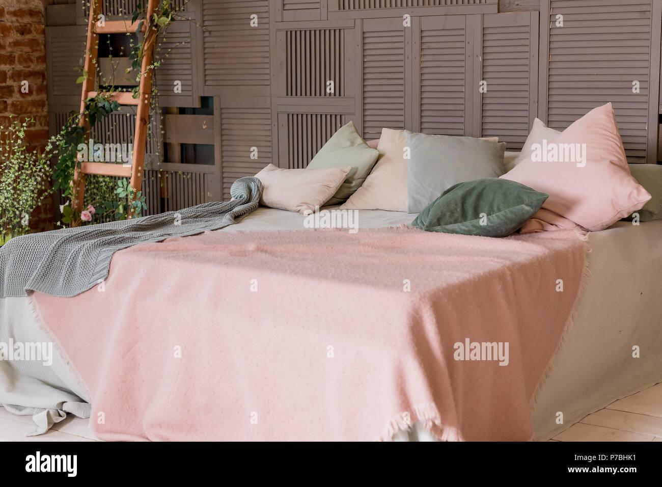 Couverture rose beige clair sur le lit avec oreillers menthe verte ...