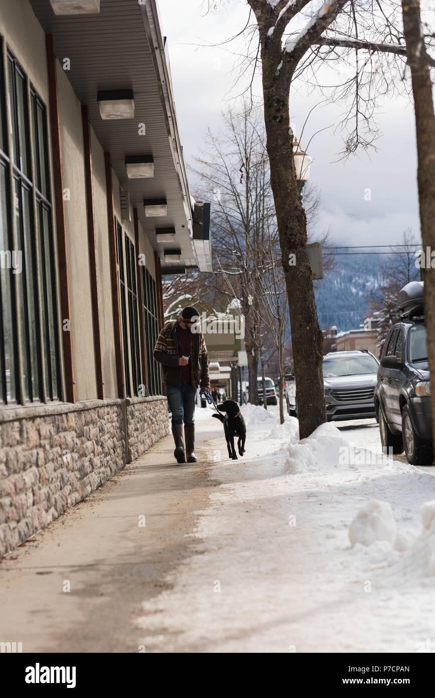 Homme marchant avec son chien sur le trottoir Photo Stock