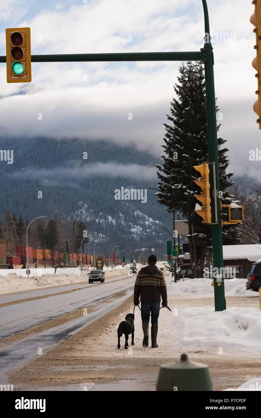 Homme marchant avec son chien sur le trottoir pendant l hiver Banque ... 61e8d80cf7e