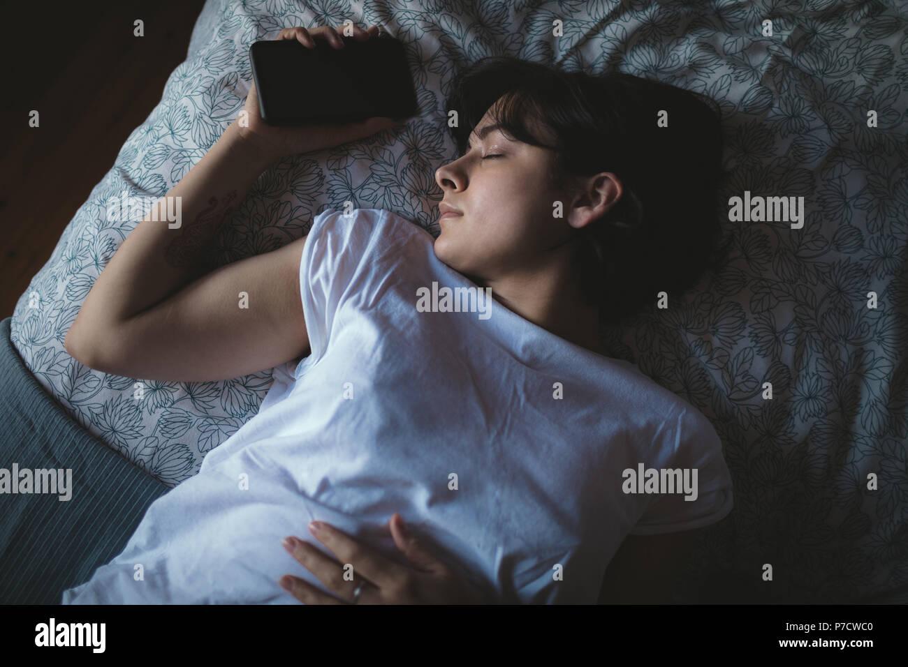 Femme avec téléphone mobile dans la chambre à coucher Photo Stock