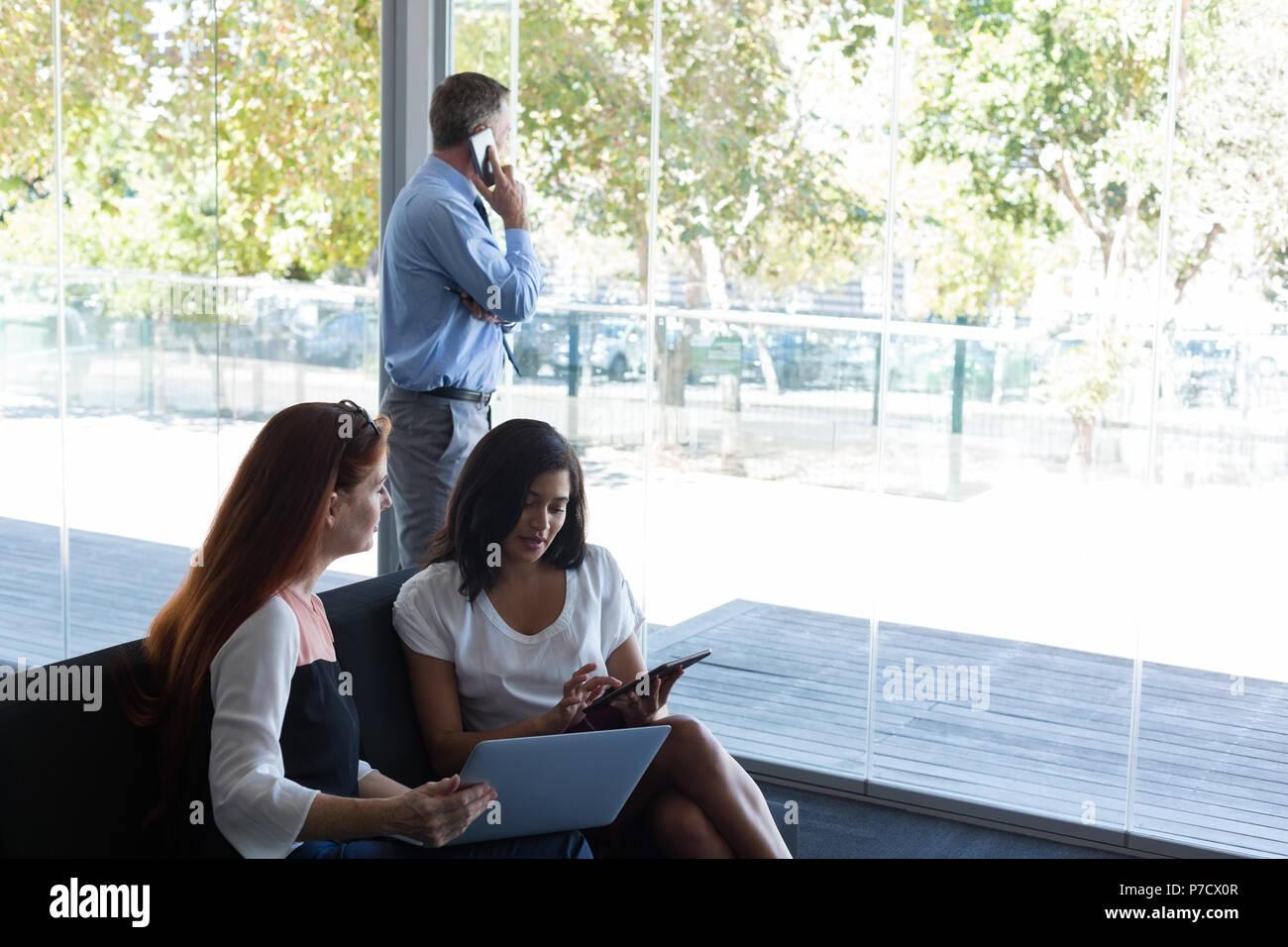 Les femmes cadres discutant sur ordinateur portable et tablette numérique Banque D'Images