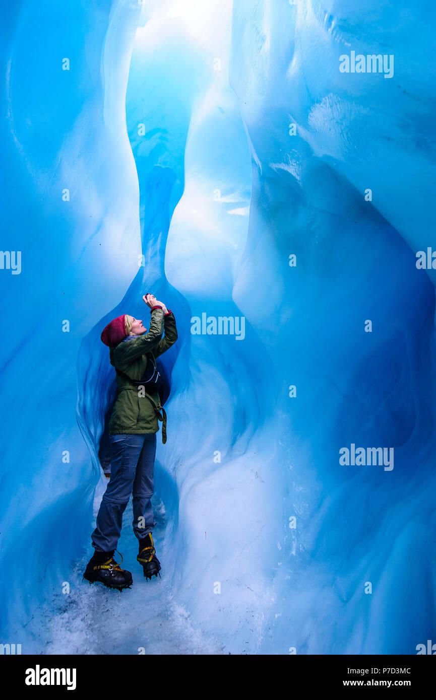 Femme de photographier à une caverne de glace dans la région de Fox Glacier, île du Sud, Nouvelle-Zélande Photo Stock