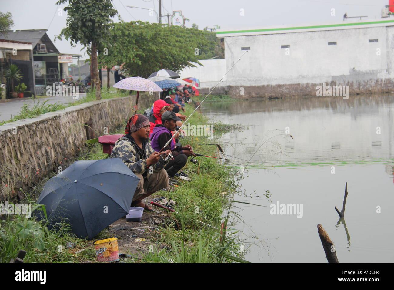 Les gens de la pêche dans un étang près de l'habitation à Bandung, Indonésie. Photo Stock