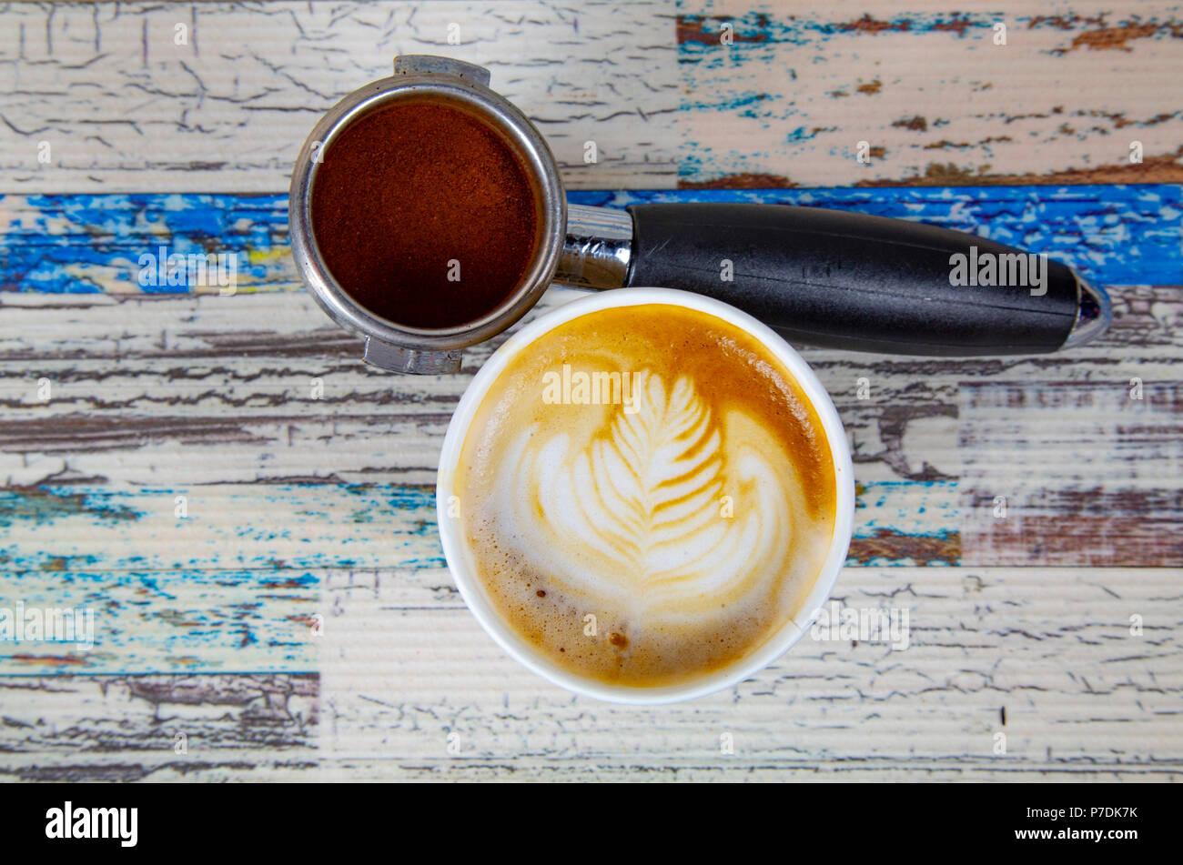 Une tasse de café au lait, cappuccino ou café expresso avec du lait mis sur une table en bois sombre avec des grains de café torréfié Photo Stock
