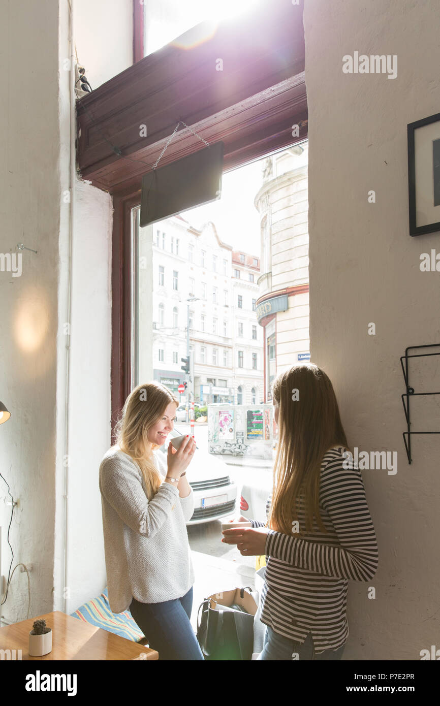 Les jeunes femmes chatting over coffee in cafe Photo Stock
