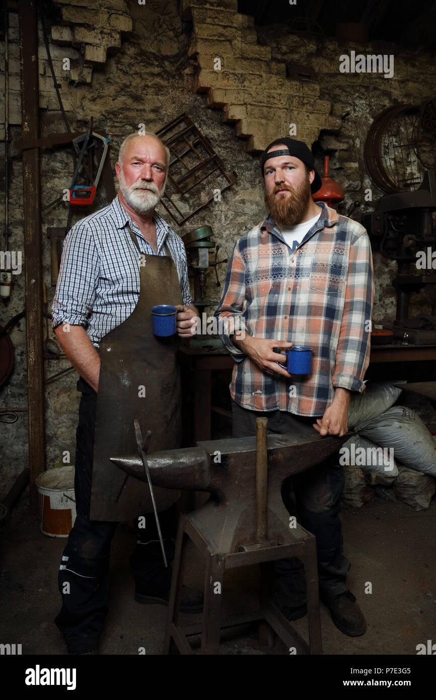 Les forgeron et fils de prendre une pause dans les forgerons shop, portrait Banque D'Images