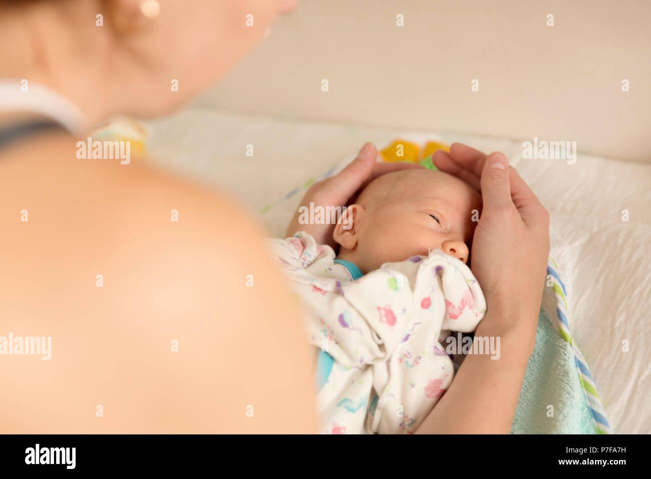 Mère réconforter un bébé nouveau-né après avoir changé une couche Photo Stock