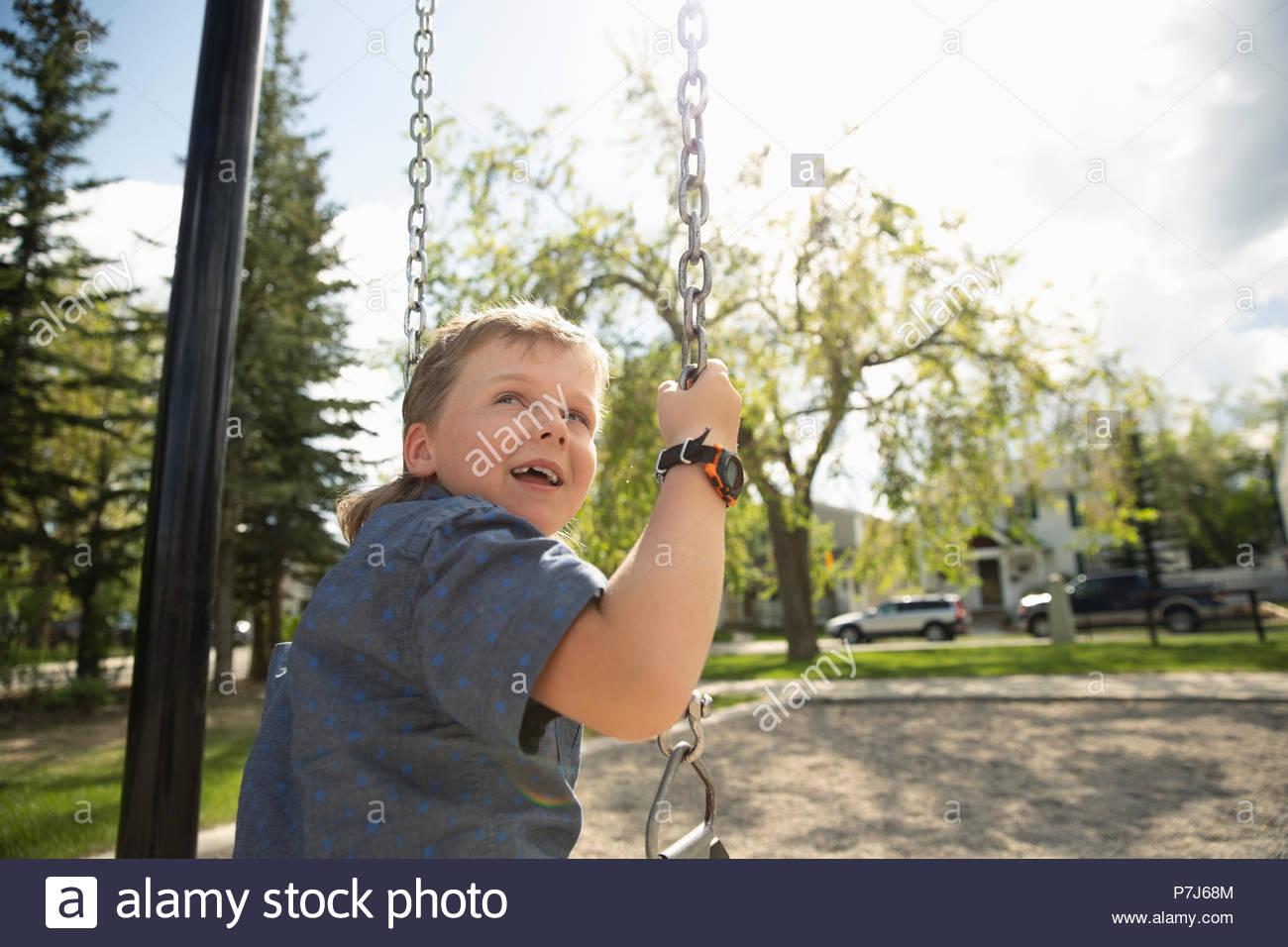 Smiling boy swinging à jeux pour enfants Photo Stock