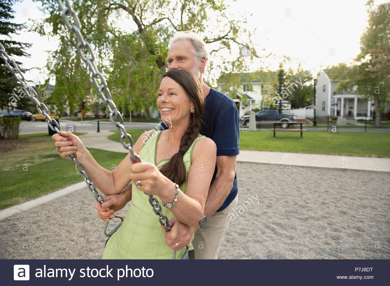 Mari Femme senior ludique poussant sur swing au jeu pour enfants Photo Stock
