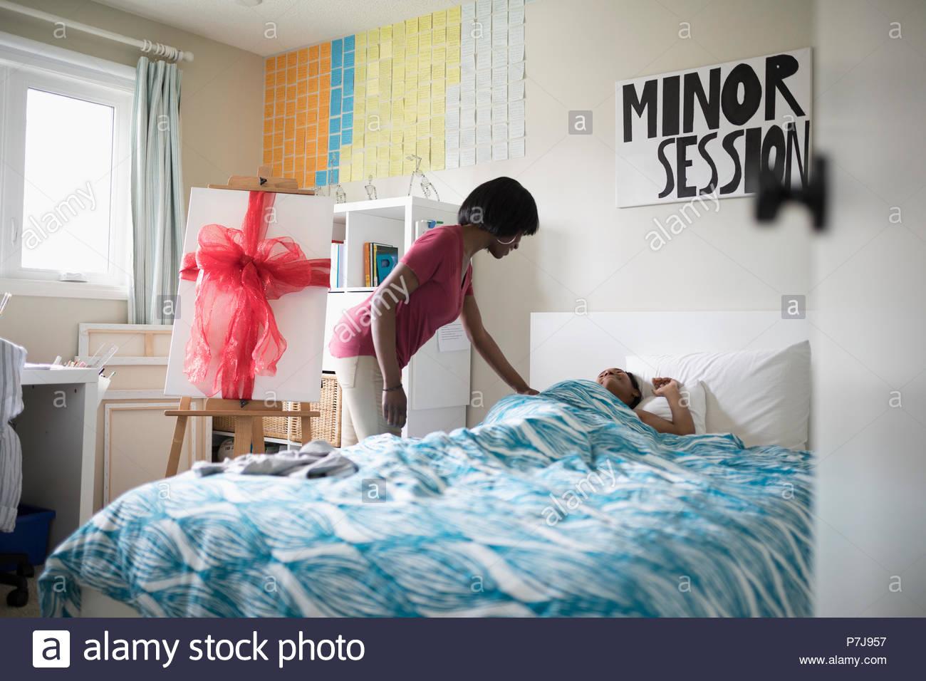 Le réveil de la mère adolescente de fille dormir dans le lit avec surprise cadeau anniversaire Photo Stock