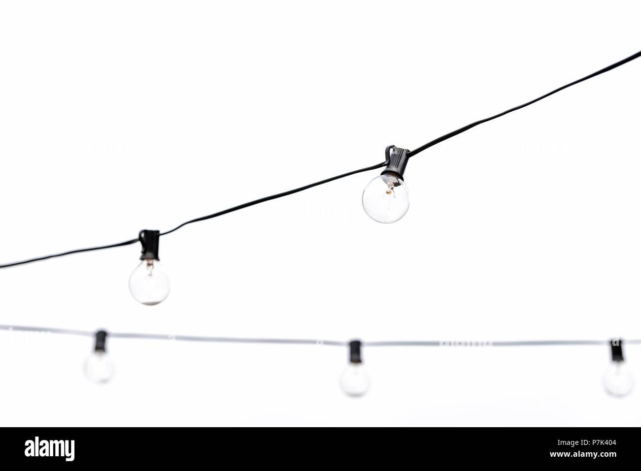 Beaucoup d'ampoules suspendues isolés contre blanc, ciel nuageux ou en studio piscine extérieure sur le toit restaurant libre Banque D'Images