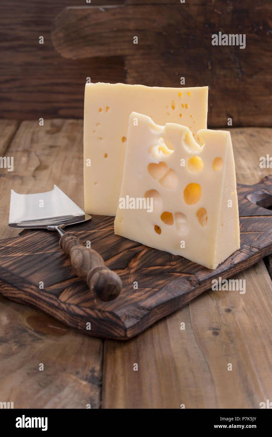 Fromage hollandais traditionnel avec des trous, sur une planche en bois vintage, fond de bois et d'un couteau pour les fromages. Les produits laitiers. Copy space Photo Stock