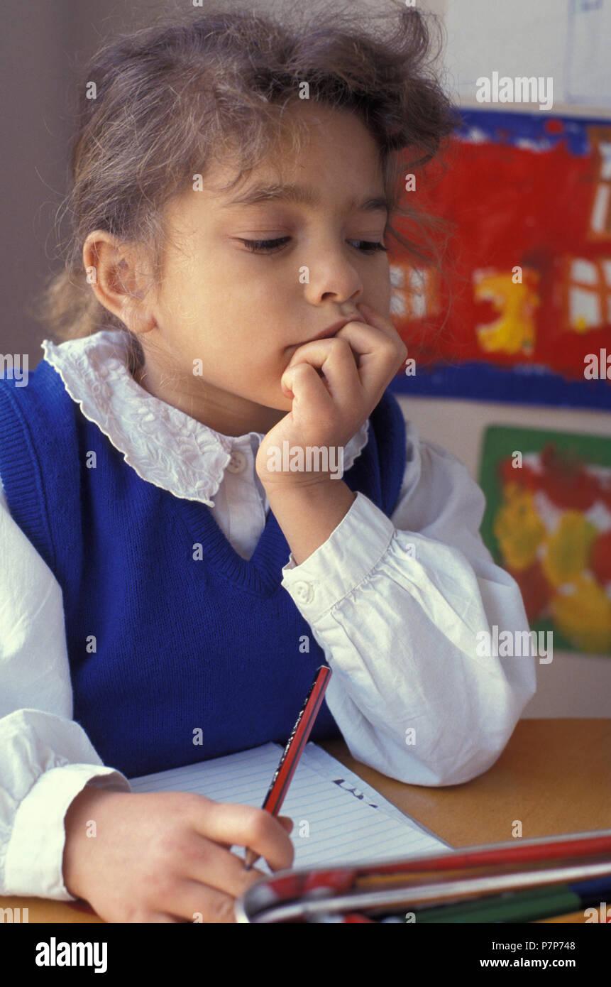 Peu contemplative écolière primaire sitting at desk Photo Stock