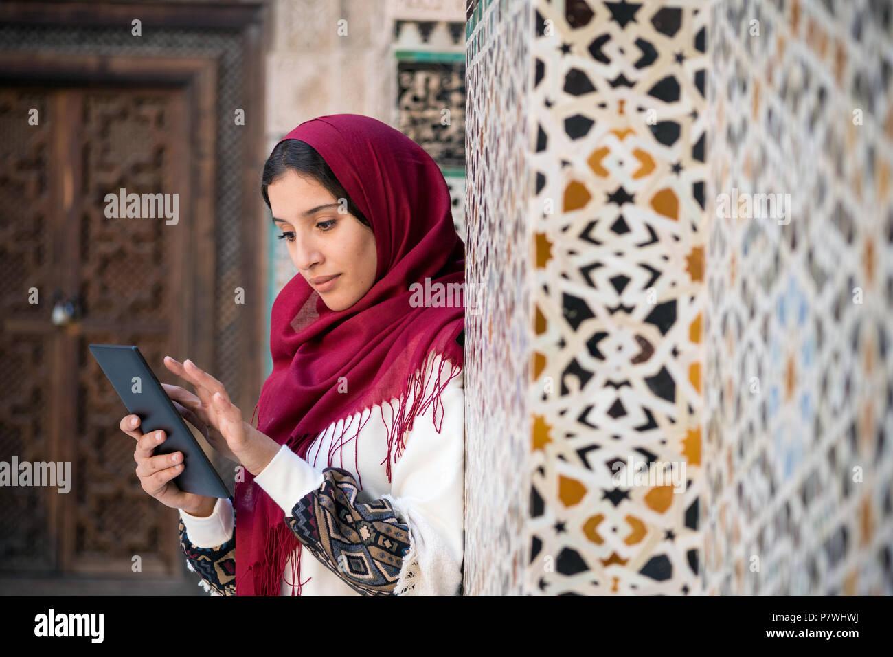 82f4a8b76fc7 Femme musulmane travaillant sur le comprimé dans des vêtements  traditionnels avec foulard rouge sur sa tête